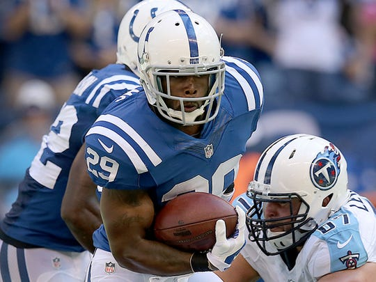 Indianapolis Colts Mike Adams returns his interception as he dodges the tackle by Tennessee Titans Andy Levitre. The Indianapolis Colts played the Tennessee Titans Sunday. September 28, 2014, afternoon at Lucas Oil Stadium.