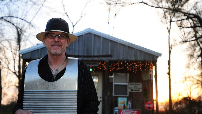 Tee Don Landry models one of his Key of Z zydeco rub boards at his home in Sunset.