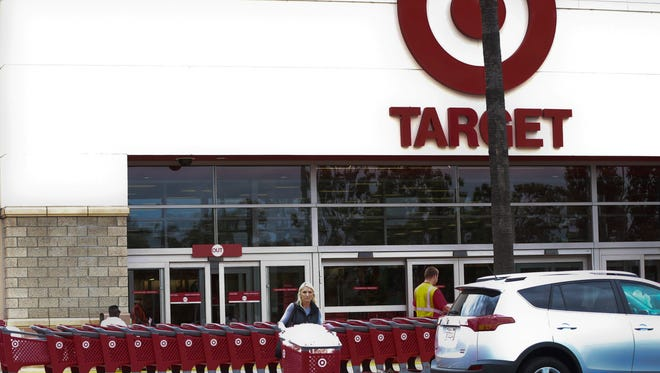 In this Thursday, May 26, 2016, photo, a woman pushes her shopping cart as an employee pulls a long line of carts outside a Target store  in Encinitas, Calif.  More than 100 retailers, including Wal-Mart and Target as well as key trade associations, are launching a new coalition aimed at fighting a Republican proposal on how imports get taxed, which they believe would harm their businesses.