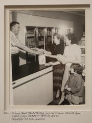 """A photograph of Harold  """"Skeets"""" Heritage showing the first sale of milk at the first Heritage's Dairy Store opening in 1957 in Westville. The photo hangs in the company offices in West Deptford."""
