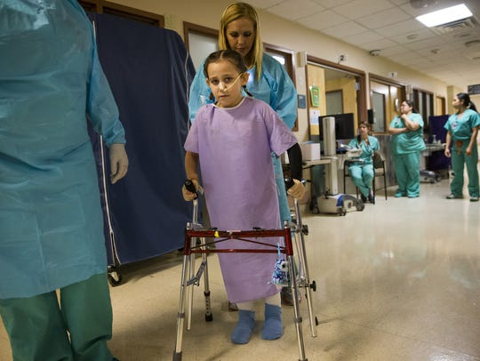 Eight-year-old Isabella McCune gets help walking from