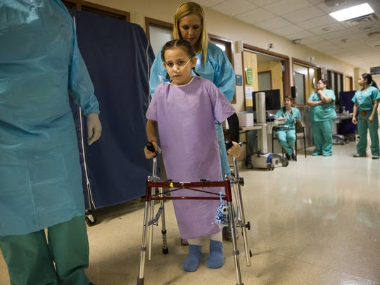 Eight-year-old Isabella McCune gets help walking from physical therapist Danika Hines at the Arizona Burn Center at Maricopa Medical Center in Phoenix.