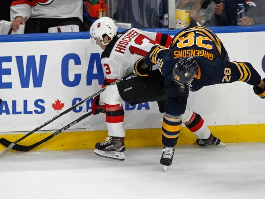 Buffalo Sabres Zemgus Girgensons (28) and New Jersey Devils Nico Hischier (13) battle along the boards during the third period of an NHL hockey game, Monday Oct. 9, 2017, in Buffalo, N.Y. (AP Photo/Jeffrey T. Barnes)