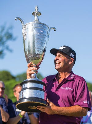 Rocco Mediate holds up the Senior PGA Championship trophy following the final round of the golf tournament Sunday at Harbor Shores Golf Club in Benton Harbor.