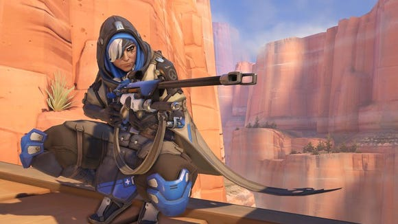 """Overwatch"" character in a desert landscape, wearing a hood and holding a sniper rifle."