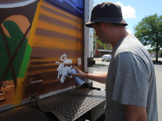 Sam Meyerson touches up the signature of his name on a bus for the Bardavon 1869 Opera House during the second annual O+ Festival in the City of Poughkeepsie. Myerson said he thought it was cool that his artwork will change based on where the bus is and the surrounding scenery.