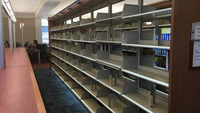Shelves at the Indianapolis Public Library's Central Library are swept clean as librarians prepare for new books.