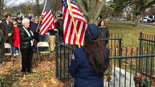 People hold flags during Burlington's annual commemoration of Veterans Day, Nov. 11, 2016, at the memorial in Battery Park to Howard William Plant, the first city resident to die in World War I.