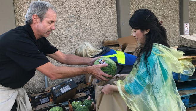 A volunteer from St. Mary's Food Bank hands out a fresh watermelon for Thanksgiving.