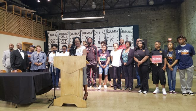 Members of the Milwaukee Community Collaborative Committee stand behind Committee Chair Markasa Tucker in a meeting Wednesday to update the public on the committee's work.