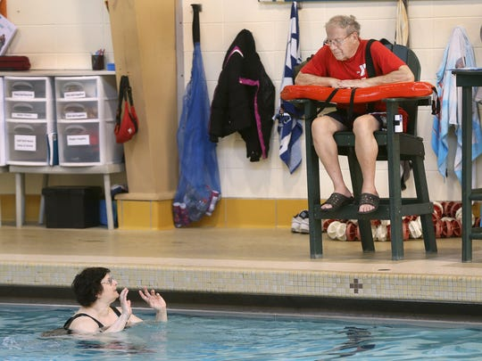 Sonny Veltre, 87, chats with NancyAnn LeMoyne, of Charlotte, during his shift as a lifeguard at the Northwest Family YMCA in Greece.