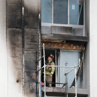 A firefighter inspects the charred outside wall of
