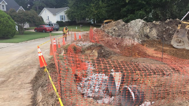 A worker at the site of repairs being done on a failed drainage system in Easley's Oak Creek subdivision