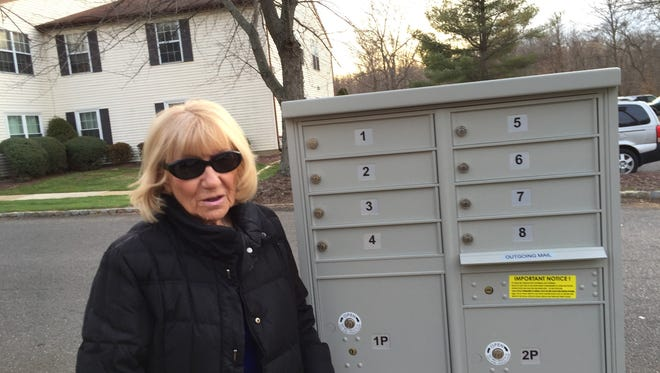 Sandy Briller, Freehold, with the new mailbox cluster installed by the U.S. Postal Service after Press on Your Side got involved.