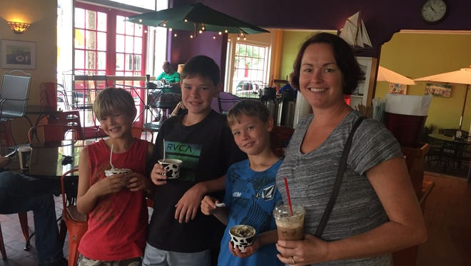 Jessica Abbott, right, and her sons Kaiden, Chase and Nathan, take a break from storm prep to enjoy ice cream and coffee at Ossorio Bakery and Cafe in Cocoa Village.