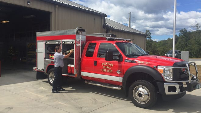 File/Ron Barnett Firefighter Anthony Still checks equipment on a truck at the Concord Road station, one of Pickens County's new fire stations.