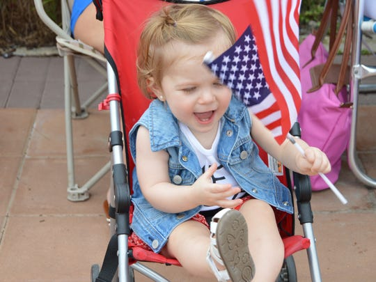 A young girl playfully waves the American flag at Bethany's July Fourth parade.