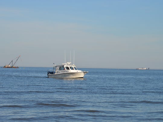 A survey boat makes a final series of runs before the