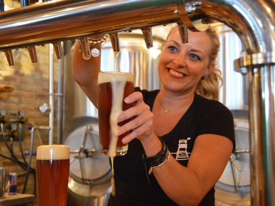 Sheena French pours a foamy brew at Dewey Beer Co.