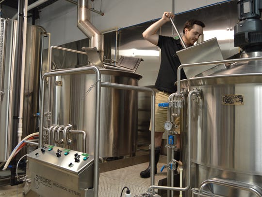 Andrew Harton stirs a batch of beer at Big Oyster Brewery in Rehoboth Beach.