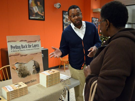 """Lawayne Childrey discusses his book, """"Peeling Back the Layers: A story of Trauma, Grace & Triumph,"""" with Patricia Iyanobor.  More than a dozen local writers displayed their books at the second annual Writers Festival at the Eudora Welty Library in Jackson Sunday."""