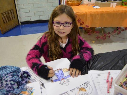 Ironia second-grader Greta Matias colors a scarecrow at the school Harvest Festival.