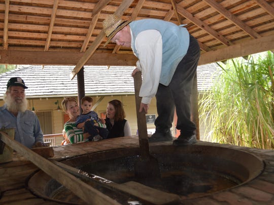 George Rogers (far right), a Kent House volunteer, stirs a pot of sugar cane syrup during a Sugar Day celebration at Kent Plantation House. Kent House, a popular tourist spot, holds various special events throughout the year.