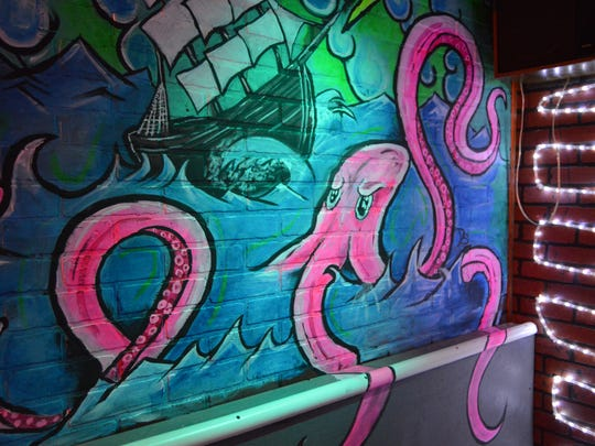 Painted artwork adorns The Alibi Room's walls.