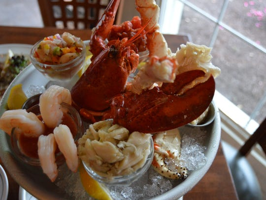 The seafood tower at Phillips' Seafood House is loaded with Maine lobster, king crab legs, jumbo lump crab meat, shrimps, oysters, clams and tuna tartar.