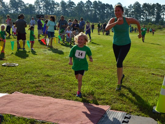Jordyn Holton runs across the finish line with her mom, Christina. (August 27, 2016)