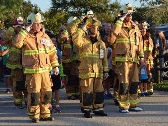 Indian River County Fire Department Chief John King, left, salutes as the Honor Guard passes.