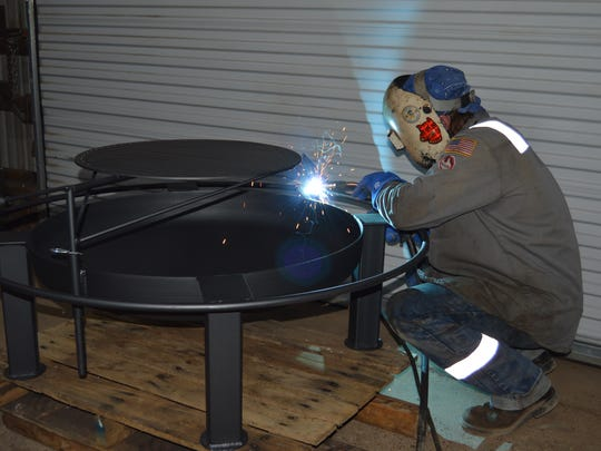 C.F. Garon, Jr. puts the finishing touch on a custom outdoor fire pit at C.F.'s Welding Service in Alexandria, La.