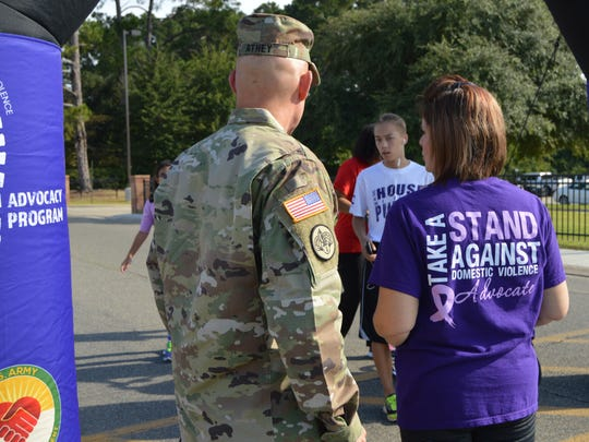 Colonel David Athey, the garrison commander of Fort Polk, stands with Kristina England, the family advocacy program manager at Polk, before a domestic violence awareness 5K race.