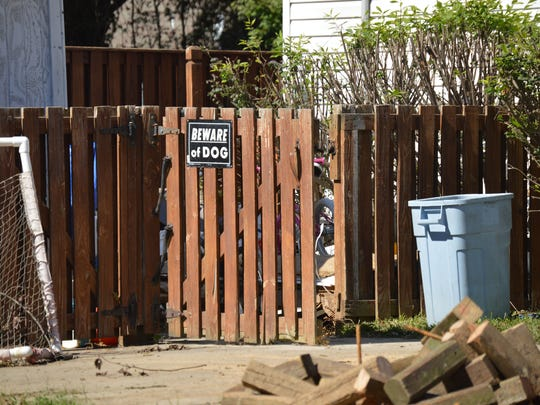 A sign states the presence of a guard dog on a fence at the Adelene Drive home where an 8-year-old girl was mauled.