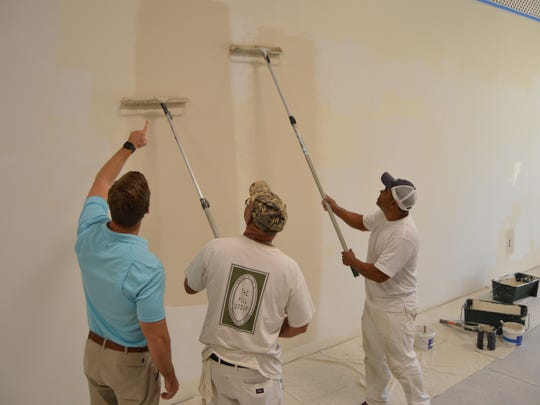 The Hill Group's Chris Hill checks on employees David Rushing and Walter Hernandez painting the wall at the Habitat ReStore.