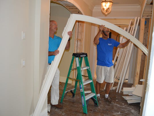 The Hill Group's Steve Burris and Habitat volunteer Jerry Weick take down a doorway molding during the deconstruction process at a John's Island residence.