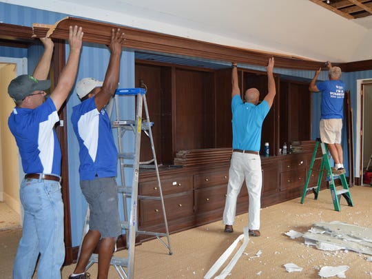 Habitat's Driver's Assistant James Young, Supervisor of Deconstruction Rito Fortes, The Hill Group's Steve Burris and Habitat volunteer Jerry Weick take down a crown molding at a John's Island residence.