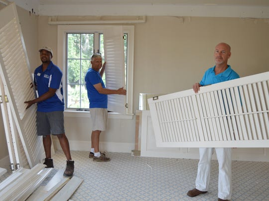 Habitat's Supervisor of DeConstruction Rito Fortes, Habitat volunteer Jerry Weick, and The Hill Group's Steve Burris with louvered shutters and doors.