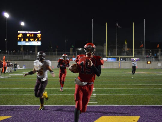 Powers North Central quarterback Jason Whitens scores his fourth touchdown of the first half in the 8-man football state championship game.