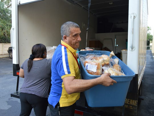 The Machados unload their truck with donated food at the church they attend with the permission and support of their pastor.