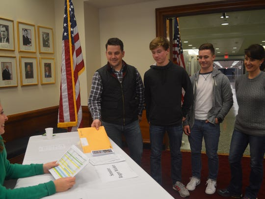 Republican State Rep. Chris Brown and his sons, Elijah, Joshua and his wife, Ryksie, pick up tickets Thursday for the presidential inauguration.