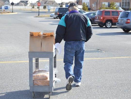 A Meals on Wheels volunteer  carries food to his car.