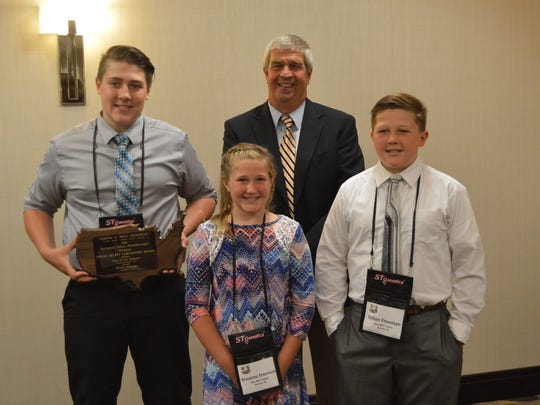 The cow that won all the production awards Jonlee Secret Langwathby 68129402 FS 2E94 was owned by these three siblings, (from left) Dalton, Breanne and Dillon Freeman of Bremen, Indiana with Brown Swiss Association President Richard Sparrow.