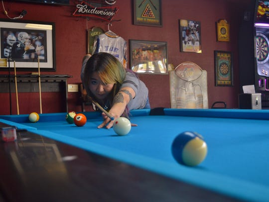 During a playful game of pool, Liz Eknoian attempts