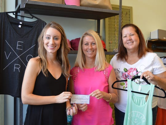 Seahorse Lane Boutique owner Audrey Mosel, left, presents a check to Friends After Diagnosis volunteer Messina Shields and board member Kat Shippee.