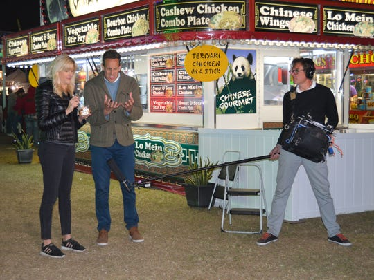 """Megan Hagy (left) from DeAnna's Food Concessions samples some fair favorites with """"Carnival Eats"""" host Noah Cappe at the Firefighters' Indian River County Fair."""
