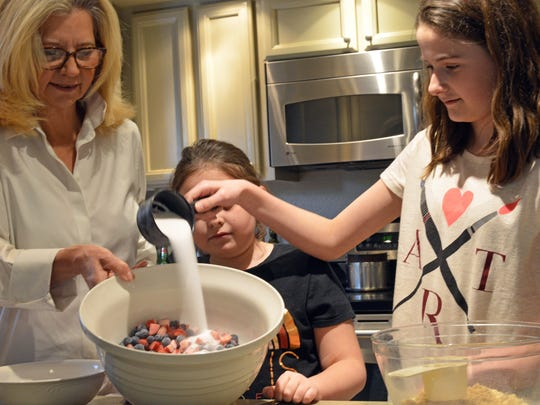 Elena Clark adds sugar to the fruit filling while making a bluebarb pie with sister Maxine and aunt Terri.