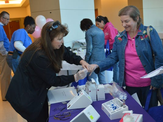 ANI Make a Difference Day Tracy Vaughn (left), an RN at Christus St. Frances Cabrini. checks the cholesterol level of Jurdine Reynolds during a Make a Difference Day Breast Cancer Awareness event held at the Women's LIfe Center at St. Frances Cabrini Hospi