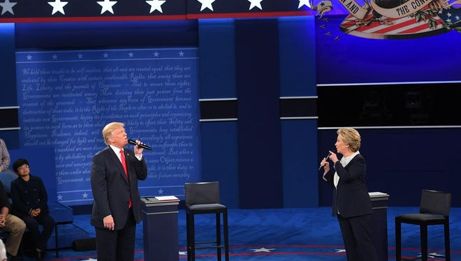 Democratic presidential candidate Hillary Clinton and Republican presidential candidate Donald Trump speak during the second presidential debate at Washington University in St. Louis on Sunday, Oct. 9, 2016.