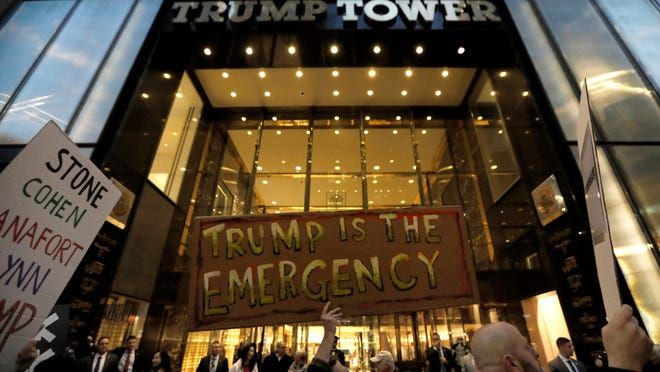 Protesters carry signs and banners outside of Trump Tower in New York in February 2019.